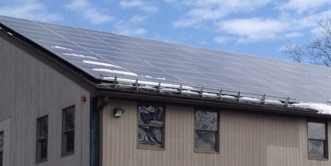 Roof with solar snow guard